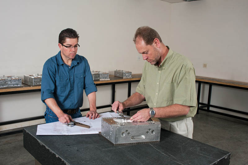 Creative engineers and technicians inspect and review tools for quality assurance.